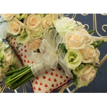 Vandela rose, lisianthus and veronica with asparagus fern, enhanced with pearls and voile ribbon.