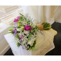 Tulip, lisianthus, freesia and gypsophila with asparagus fern and panicum grass enhanced with rustic binding.