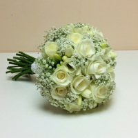 Akito rose, freesia and gypsophila enhanced with pearl clusters.