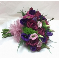 Blueberry rose, lisianthus and trachelium with asparagus fern, enhanced with a colour coordinated voile ribbon bow.