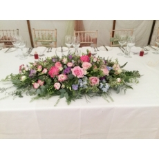 David Austin roses, Avalanche Pink and All 4 Love roses, delphinium, limonium, veronica, lisianthus and million bells with coordinating foliage.
