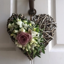 Memory Lane rose, freesia, spray rose, lisianthus, veronica and gypsophila with coordinating foliage on a rustic heart.