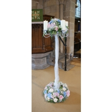 Tall candelabra with Sweet Avalanche rose, hydrangea, lisianthus and gypsophila with coordinating foliage enhanced with LED candles.
