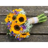 Sunflower, cornflower, limonium and gypsophila with coordinating foliage and bound with hessian and lace ribbon.