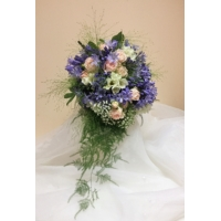 Agapanthus, freesia, spray rose and gypsophila with trailing asparagus fern bound with coordinating voile ribbon.